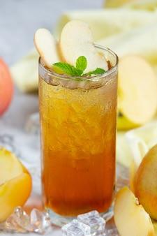 Bebida de té helado de manzana con manzanas frescas.