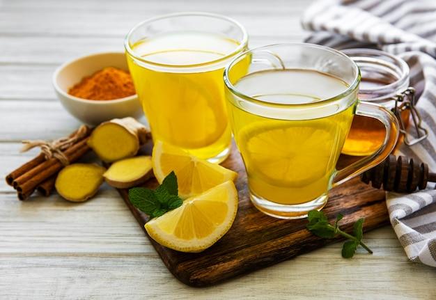 Bebida tónica energética con cúrcuma, jengibre, limón y miel sobre un fondo de madera blanca