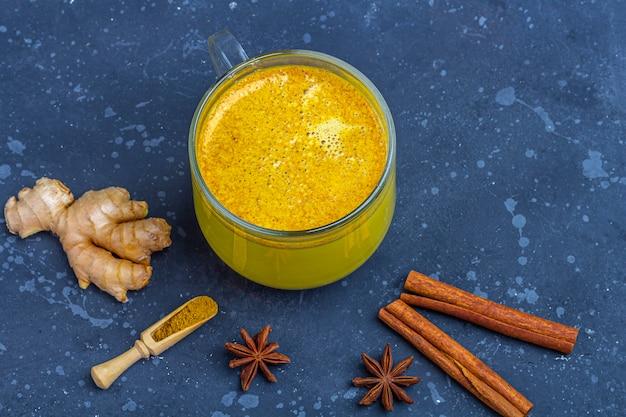 La bebida tradicional india de la leche de cúrcuma es leche dorada en una taza de vidrio con cúrcuma y raíz de jengibre, canela, anís estrella en la oscuridad