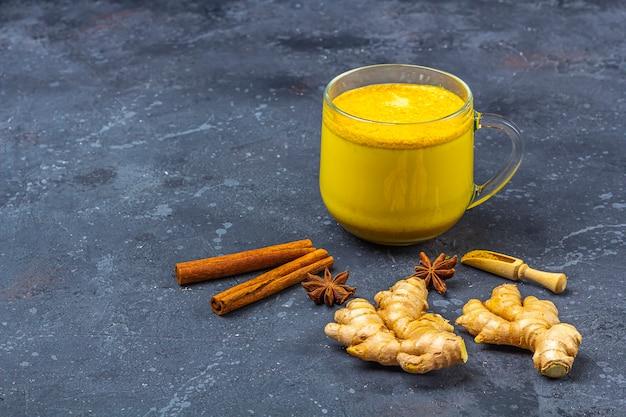 Bebida tradicional de la india, la leche de cúrcuma es leche dorada en una taza de vidrio con cúrcuma y raíz de jengibre, canela, anis star