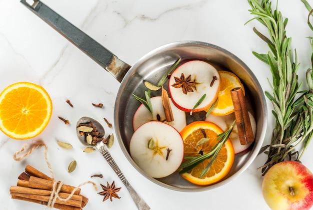 Bebida tradicional de invierno y navidad, ingredientes para vino caliente bebida caliente con cítricos, manzana y especias en una cacerola de aluminio sobre mesa de mármol blanco. vista superior de copyspace