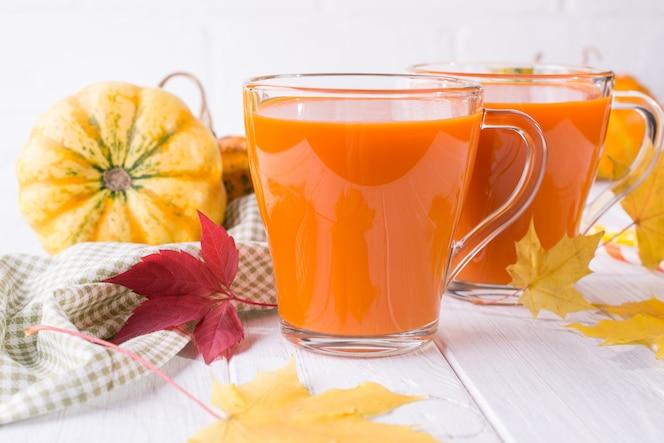 Bebida tradicional de otoño. vasos de vidrio de jugo de calabaza, calabazas y hojas de arce caídas