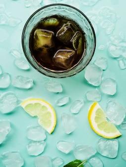Bebida en vaso junto a limones y bloques de hielo.