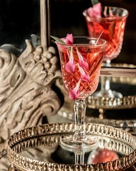 Una bebida en un vaso con pétalos de rosa en una bandeja