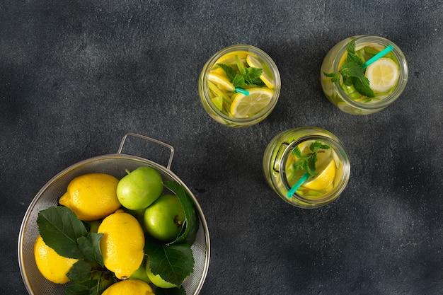 Bebida de verano sin azúcar. limonada fresca con manzanas y limón en una vista superior oscura