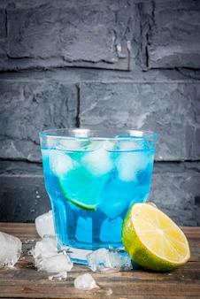 Bebida de verano colorida bebida de cóctel de alcohol de laguna azul helado con fondo de corteza de lima y menta