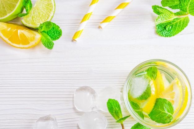 Bebida de verano mojito con lima, limón y menta, con cubitos de hielo.