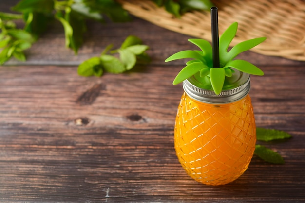 Bebida del verano, vidrio de jugo de piña en la tabla de madera.