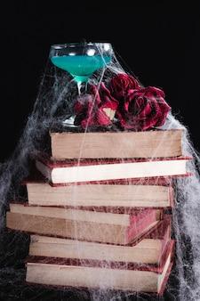 Bebida verde con rosas, libros y telaraña
