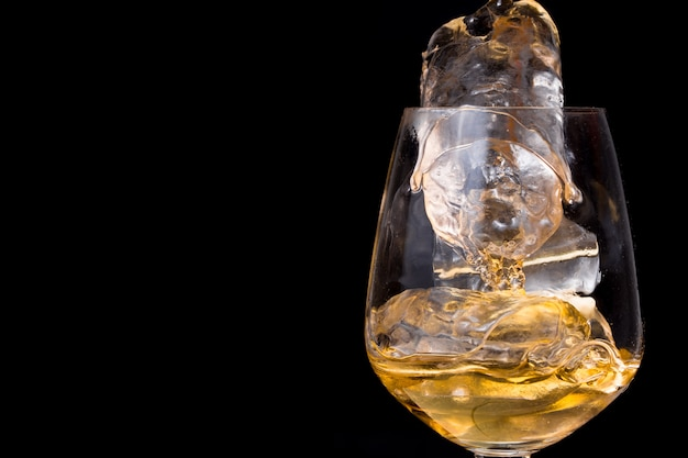 Bebida de whisky con hielo sobre fondo negro