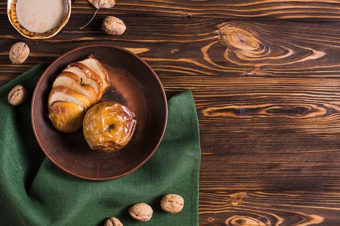 Bebida y nueces cerca de manzanas y servilletas al horno