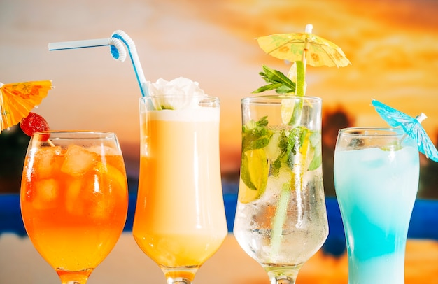 Bebidas amarillas suaves de naranja con rodajas de fresa y menta en vasos