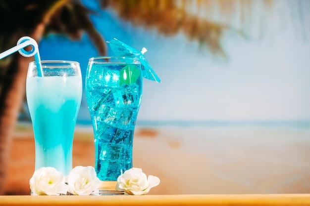 Bebidas azules con paja en sombrilla decorada con vasos y flores.