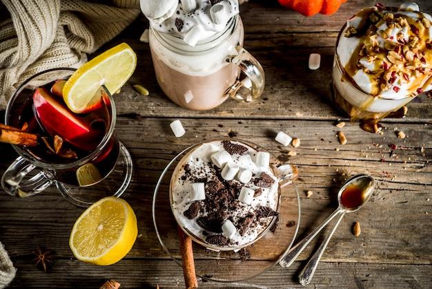 Bebidas calientes de otoño invierno, chocolate caliente, café con leche de calabaza, café con leche con caramelo y café de maní, vino caliente, fondo oscuro acogedor