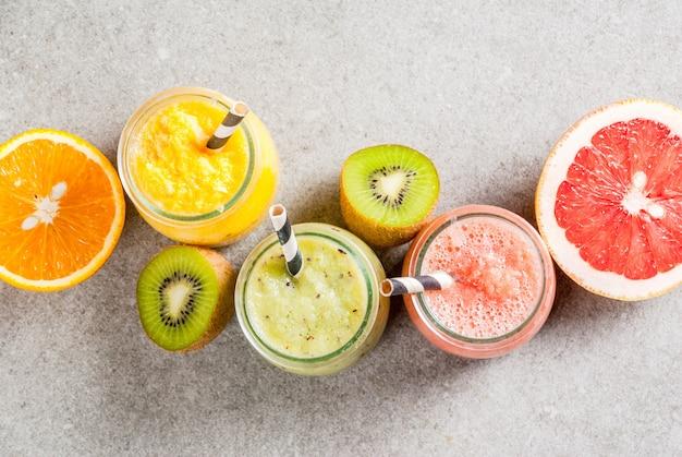 Bebidas dietéticas de desintoxicación, batidos tropicales caseros: kiwi, naranja, pomelo, en frascos con ingredientes, sobre una mesa de piedra gris. vista superior de copyspace