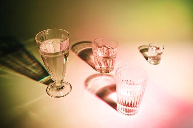 Bebidas en los diferentes tipos de vasos con sombra sobre fondo coloreado.