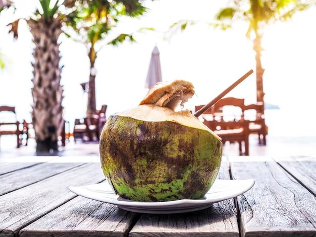 Bebidas frescas de agua de coco colocadas en una mesa de madera junto al mar en verano