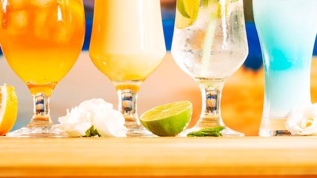 Bebidas frescas de color amarillo anaranjado brillante azul y rodajas de limón menta flor menta
