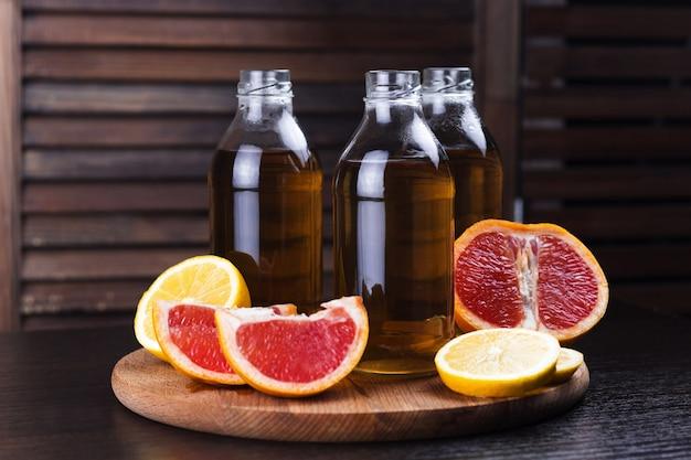 Bebidas frescas de limón y pomelo en botellas de vidrio.