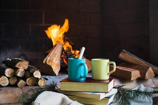 Bebidas y libros junto a la chimenea de fuego.