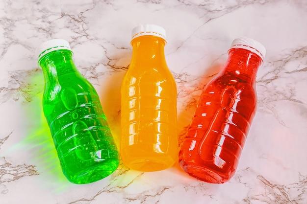 Bebidas de limonada de colores naturales en botellas de plástico en mármol