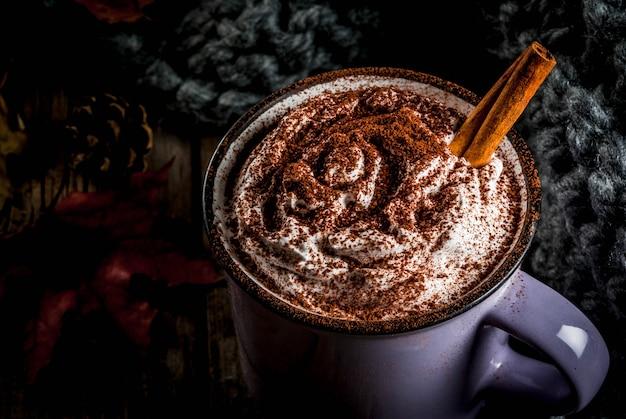 Bebidas de otoño, chocolate caliente o cacao con crema batida y especias (canela, anís), en la vieja mesa de madera rústica, con una cálida manta acogedora, bayas de heno y hojas de copyspace
