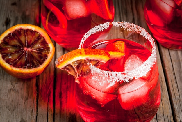 Bebidas refrescantes de verano. cóctel margarita naranja sangrienta, en vasos sobre una mesa rústica de madera con una guarnición de naranja.