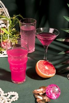 Bebidas rosas junto a artículos femeninos en mesa.