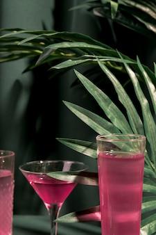 Bebidas rosas junto a plantas tropicales.