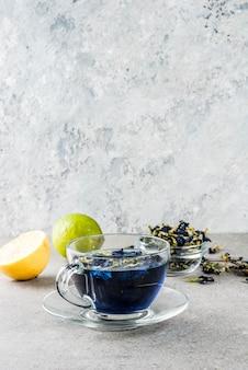 Bebidas saludables, té de flor de guisante de mariposa azul orgánico con limas y limones, espacio de copia de fondo de hormigón gris