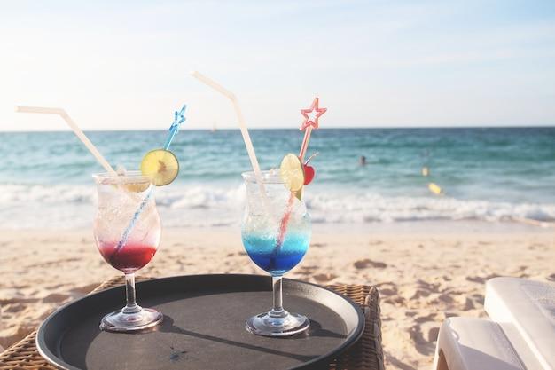 Bebidas de verano en mesa y playa.