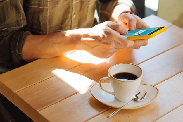 Bebiendo café. cerca de una taza de café medio llena mientras está bebido por un joven agradable