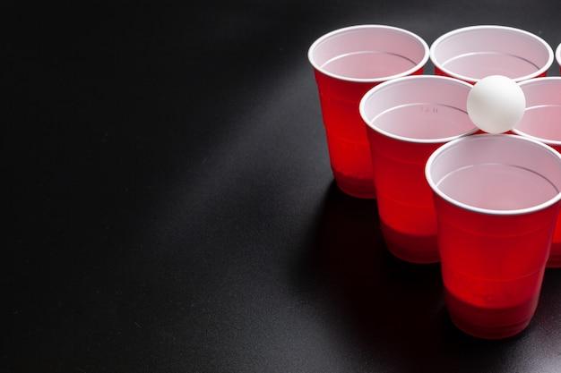 Beer pong juego universitario sobre fondo negro