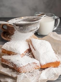 Beignet espolvoreado con azúcar glas sobre una mesa de madera con café y leche.