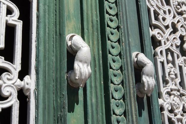 Beja, alentejo, portugal. detalle de una puerta de madera. cada aldaba de la puerta tiene la forma de una mano.