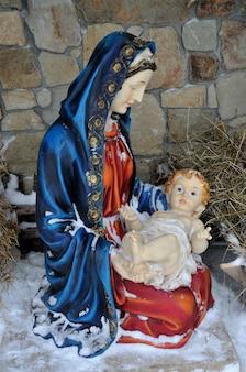 Belén nacimiento de jesús estatuilla de maría con jesús recién nacido en el heno cubierto de nieve