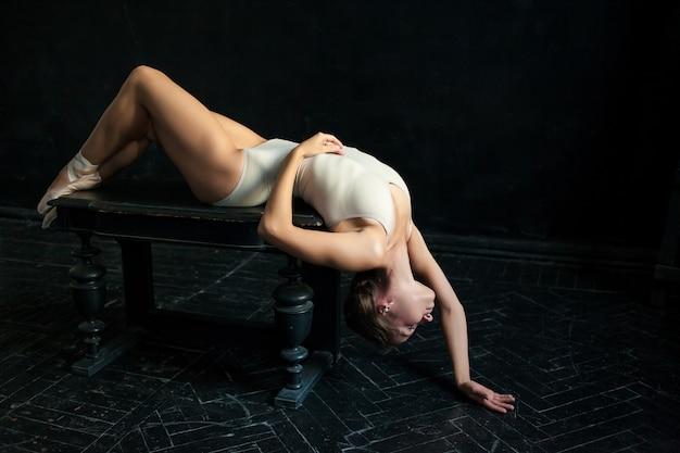 La bella bailarina posando contra la oscuridad