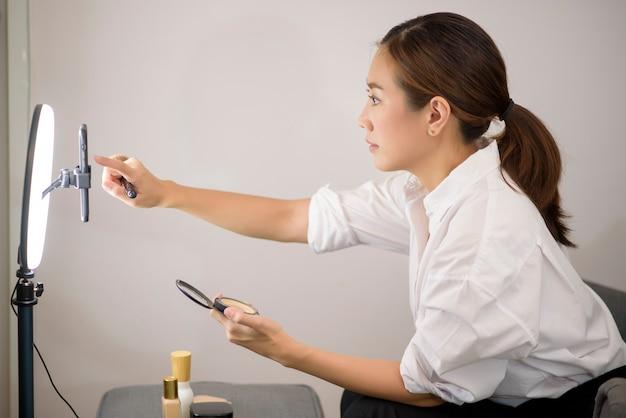 Una bella bloguera de maquillaje asiática está transmitiendo en vivo cómo maquillarse la cara en su casa