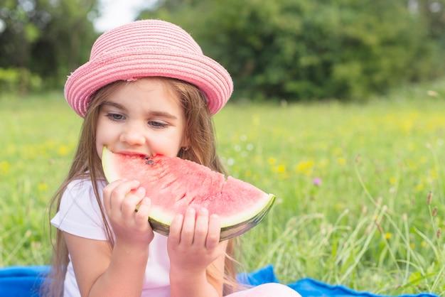 Bella comiendo rebanada de sandía sentado en el parque