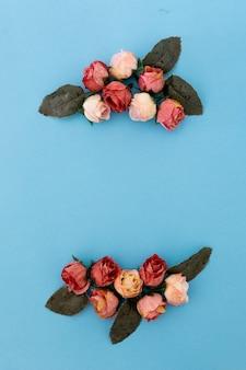 Bella composición con rosas y pétalos sobre fondo azul con copyspace
