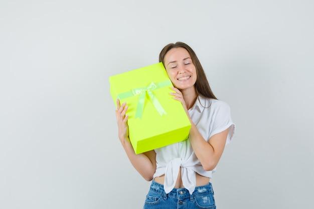 Bella dama abrazando la caja de regalo en blusa blanca, jeans y mirando amado, vista frontal.