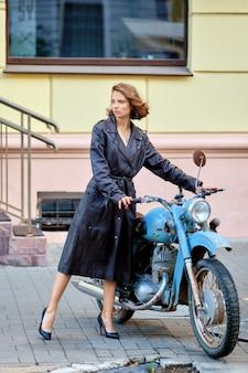 Bella dama en abrigo de cuero largo con moto antigua vintage
