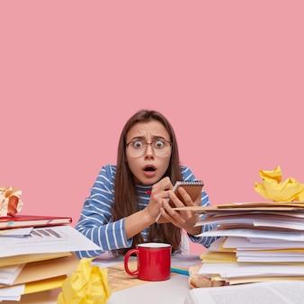 Bella dama aterrorizada tiene expresión asustada, usa anteojos grandes y ropa a rayas, toma notas en el bloc de notas, escribe una lista de tareas pendientes, ocupada con el trabajo