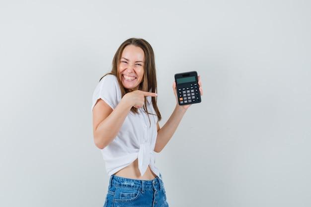 Bella dama en blusa blanca, jeans apuntando a la calculadora y mirando alegre, vista frontal.