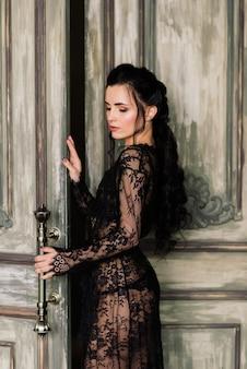 Bella dama en elegantes bragas negras y bata acostada en la cama de su dormitorio.