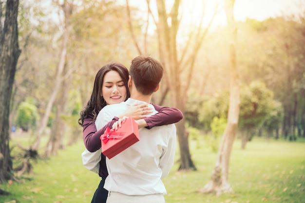Bella dama se inclina al hombro del hombre mientras él la abraza para regalar.