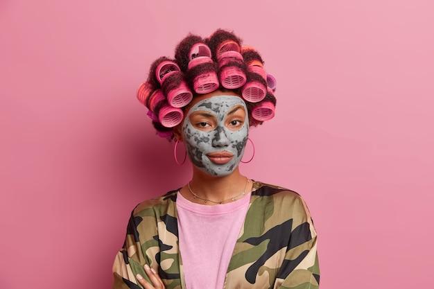 Bella dama con máscara para el cuidado de la cara con rizadores de pelo aislados