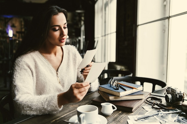 Bella dama mira fotos antiguas sentado en la mesa de café