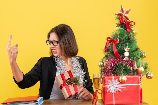 Bella dama de negocios en traje con gafas apuntando hacia arriba con enojo y sentado en una mesa con un árbol de navidad en la oficina en amarillo