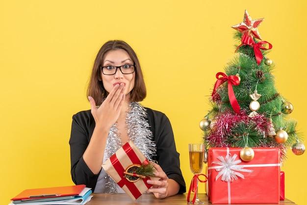 Bella dama de negocios en traje con gafas enviando besos y sentada en una mesa con un árbol de navidad en la oficina en amarillo
